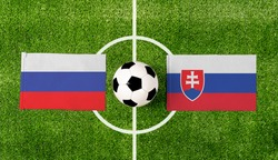 Top view ball with Russia vs. Slovakia flags match on green soccer field.
