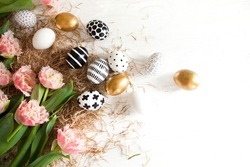 Top view beautiful golden and black-white modern easter eggs lie on a white wooden table next to hay and pink fringed tulips. Stylish easter concept. Spring card. Copyspace