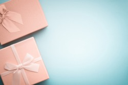 Top view beige gift boxes with ribbons tied with a bow on a light blue background in pastel colors/