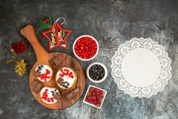 top view berry cakes and chocolates on chopping board xmas toys bowls with pomegranate raisins and raspberries white lace doily on grey-white background with copy space