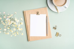 Top view blank paper Notebook, flowers, golden paper binder clips, cup of coffee and pen. Desktop mock up, Flat lay of green working table background with office equipment, mockup greeting card