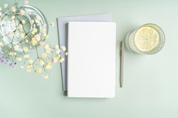 Top view blank paper Notebook, flowers, water with lemon and pen. Desktop mock up, Flat lay of green working table background with office equipment, mockup greeting card