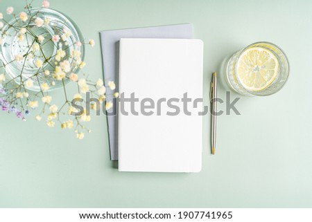 Top view blank paper Notebook, flowers, water with lemon and pen. Desktop mock up, Flat lay of green working table background with office equipment, mockup greeting card stock photo