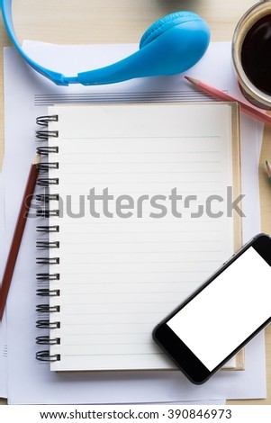 top view blank screen of mobile phone on notebook and wooden desk with pencil and headphone #390846973