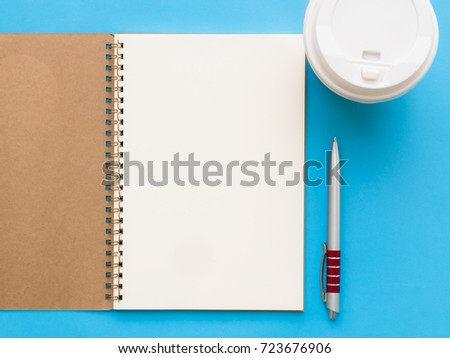 Top view blank spiral note book with coffee cup and pen on blue background #723676906