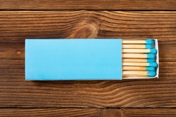 top view blue color matchbox with blue match sticks on a wood table