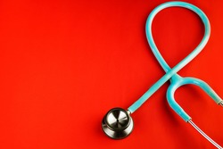 Top view blue stethoscope on red background. For heart or health care check up concept, selective focus, copy space