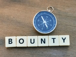 Top view BOUNTY crossword by square letter tiles against wooden background with compass.