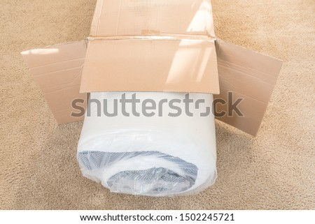 Top view brand new roll-packed spring mattresses on carpet floor of apartment bedroom in Texas, America. Foam and latex hybrid material mattress being unboxed from cardboard box Сток-фото ©