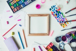 Top view Bright workplace of creative artist mockup. Blank canvas surrounded by variety of drawing supplies. Art, workshop, painting, drawing, inspiration, craft, creativity concept. Art therapy