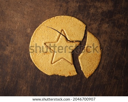 Top view broken Dalgona or Ppopgi candy, honeycomb toffee sugar candy with star shape on brown wooden background