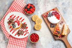 top view cake with chocolate on oval plate berry cake and waffles on cutting board bowls with pomegranate raspberry candies biscuits kitchen towel on marble ground