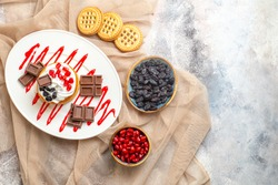 top view cake with chocolate on white oval plate bowl with cornels and raisins biscuits on beige tablecloth on marble ground with copy space