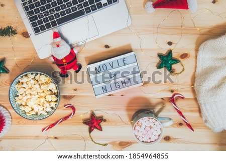Top view Christmas Movie night concept. Flat lay composition with Movie night message on the board, laptop, popcorn bowl, decor, a cup of cocoa with marshmallows and warm plaid on wooden background