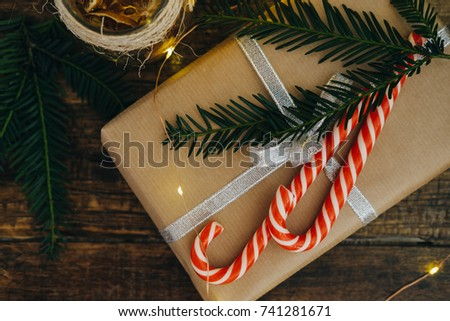 Top View Christmas present with candy canes and Fir tree branch on dark wooden background. Selective focus