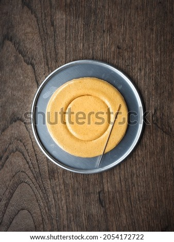 Top view Circle shaped Dalgona or Ppopgi honeycomb sugar candy in round tin tray with needle on wooden background