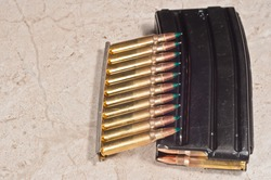 top view, close distance, of 5,6 mm ammo on a striper clip and a 20 round magazine, filled with ammo