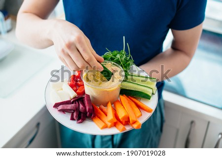 Top view close up man's hand dipping cucumber stick in hummus on the kitchen. Hummus served with raw vegetables on the plate. Healthy food lunch. Vegetarian and vegan food diet. Soft selective focus Сток-фото ©
