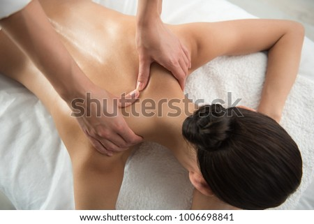 Top view close up of masseuse hands massing female neck skillfully