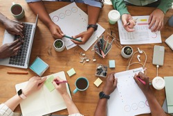 Top view close up of multi-ethnic group of people working together at cluttered wooden table with coffee cups, mugs and stationary items, teamworking or studying concept, copy space