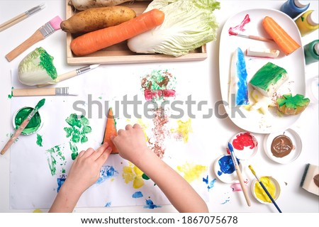Top view close up of toddler boy child hands, kid making artwork from vegetable stamping at home, Fun art and crafts for toddlers, Children's Art Project