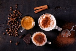 top view, close-up, on the dark wooden background, some types of espresso-based drinks, latte macchiato and cappuccino with a sprinkling of cocoa powder.