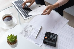Top view close up woman calculating bills, money, loan or rent payments, using laptop, online banking service, sitting at table, female holding receipt, planning budget, managing expenses, finances