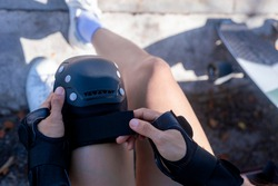 top view Close up Woman surf skate board putting on knee protector pads on her arm and wearing wrist guards. On morning young women putting protective guard before play extreme surf skate board.