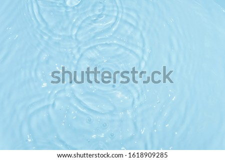 top view Closeup blue water rings, Close-up water droplets affect the surface, forming rings on the surface. reflections in water. Radial waves from a rain on water. Circles and rings on the puddle.