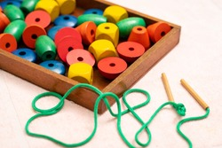 Top view closeup of colorful wooden beads, needle in the tray. Educational toys, Montessori sensorial activity for toddlers and baby, Hands eyes coordination, Cognitive skills, Children development.