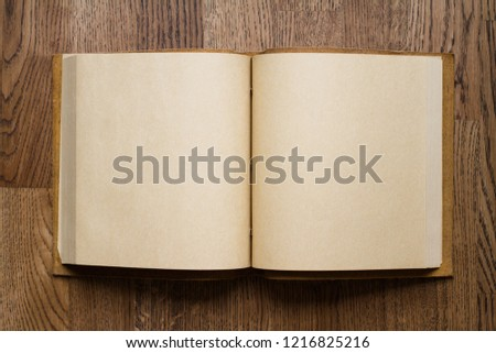 top view closeup of open book with leather covers and empty white pages on brown wooden parquet floor background #1216825216