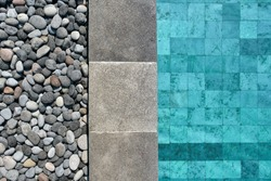 Top view closeup photo of a swimming pool with blue water outdoors. It has a tiled gray edge which is decorated with pebbles. Horizontal.