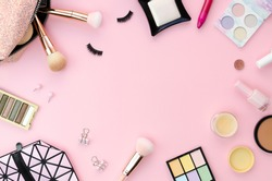 Top view colorful frame mockup with various makeup products on a pink background with copy spoace. Female workdesk concept