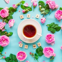 Top view creative layout with Tea time lettering with wooden blocks, cup of hot tea and fresh pink tea rose flowers, buds, petals, leaves on the blue background. Flat lay. Square card. Copy space