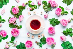 Top view creative layout with Tea time lettering with wooden blocks, cup of hot tea and fresh pink tea rose flowers, buds, petals, leaves on white background isolated. Flat lay. Copy space