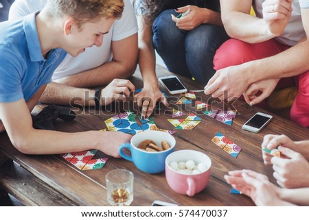 Top view creative photo of friends sitting at wooden table. Friends having fun while playing board game