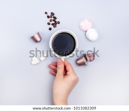 Top View Cup of Coffee Coffee Capsule Coffee Beans Sugar in Shape of Hearts Marshmallow Coffee Concept Background Blue Background Female Hand Holding Cup Flat Lay