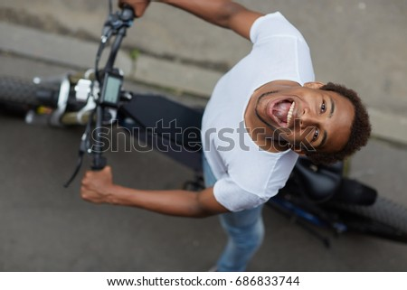 Top view - cute positive african american guy in casual clothes looks at camera and laughs sitting on e-bike on urban asphalt road