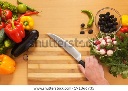 Top View Cutting Board. Vegetables and kitchen knife on cutting board
