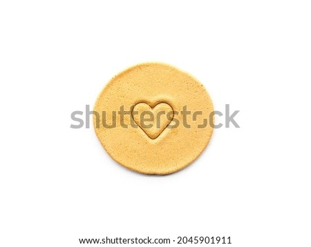 Top view Dalgona sugar candy with heart shape stamp on white background