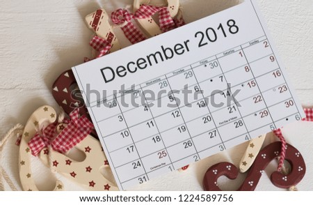 Top view: December 2018 calendar with holiday dates and moon days is on a white wooden table with Christmas decorations. Concept: Merry Christmas and Happy New Year card.