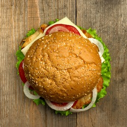 Top view delicious hamburger on wooden background. Fastfood meal