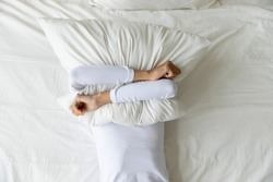 Top view depressed woman covering face with pillow, lying on bed at home alone, frustrated unhappy young female suffering from insomnia, mental or relationship problems, break up or divorce