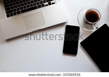 Top view desk work laptop smart phone tablet and coffee cup notepad in home office.