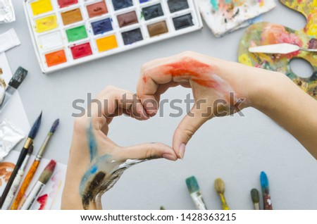 Top view dirty hands making a heart with painting materials