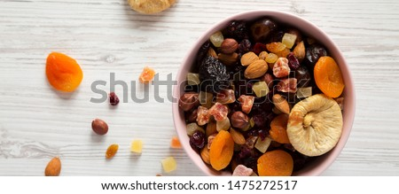 Top view, dried fruits and nut mix in a pink bowl on white wooden surface. Overhead, from above, overhead.  #1475272517