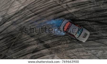 Top view drifting car, Aerial view photo from flying drone of drifting car on race track.