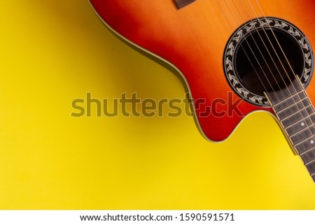 Top view electro acoustic guitar over yellow background. Musician and guitarist player concept.