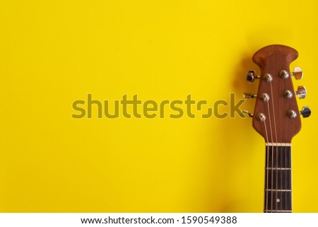 Top view electro acoustic guitar over yellow background. musician guitarist  concept.