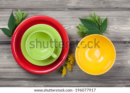 Top view empty red plate, yellow bowl and green cup on rustic wooden table with spring leaf and flower